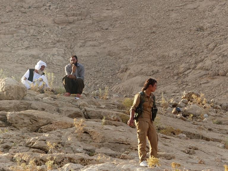 Una joven luchadora de YPJ-Shengal vigilando la marcha del aniversario junto con ancianos yazidíes.
