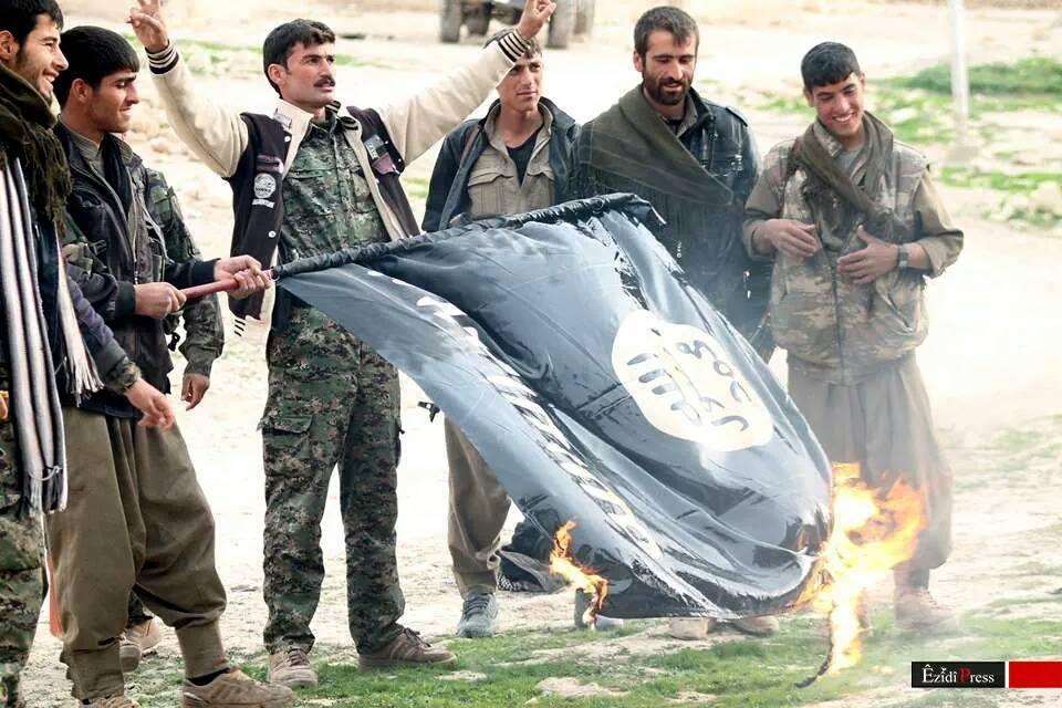 Luchadores de las YBS y el PKK queman una bandera de ISIS después del éxito de una operación en el este de Shengal contra el Estado Islámico