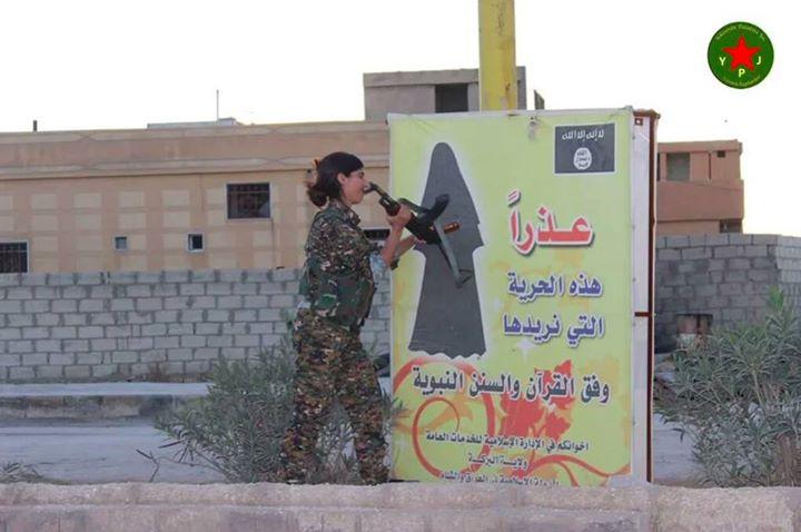 Una luchadora de las YPJ-Shengal rompe un letrero de ISIS que impone a las mujeres cubrirse con el niqab